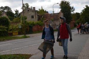 dwóch wolontariuszy idą z workami sprzątać las