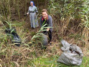 dwie wolontariuszki sprzątają las