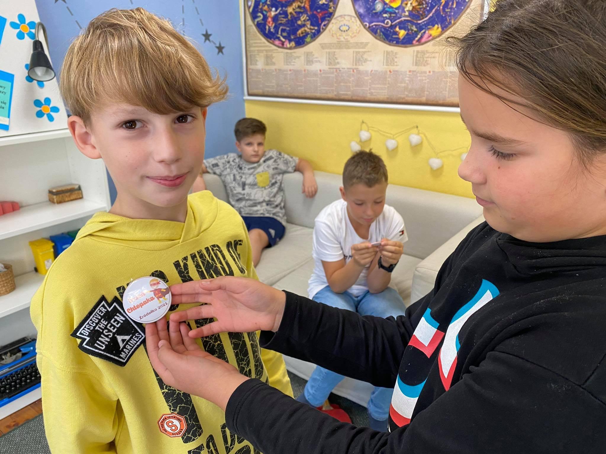 dziewczynka przypina chłopakowi ręcznie zrobioną przypinkę