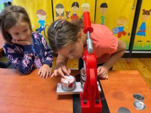 dwie dziewczynki robią przypinki