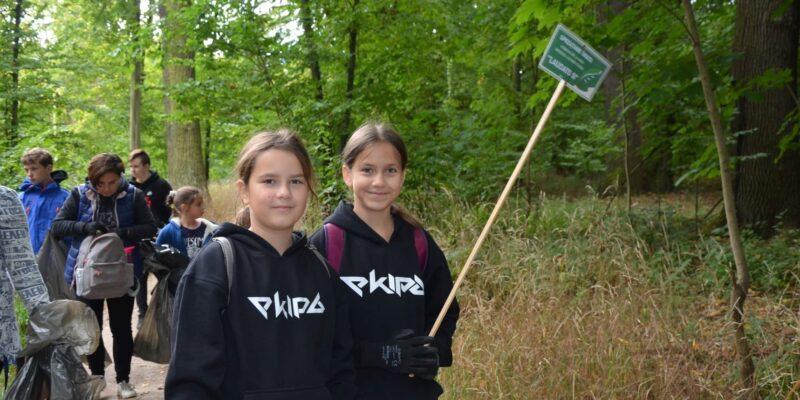 dwie dziewczynki idą sprzątać do lasu