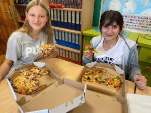 Dwie wolontariuszki w Źródełku jedzą pizzę