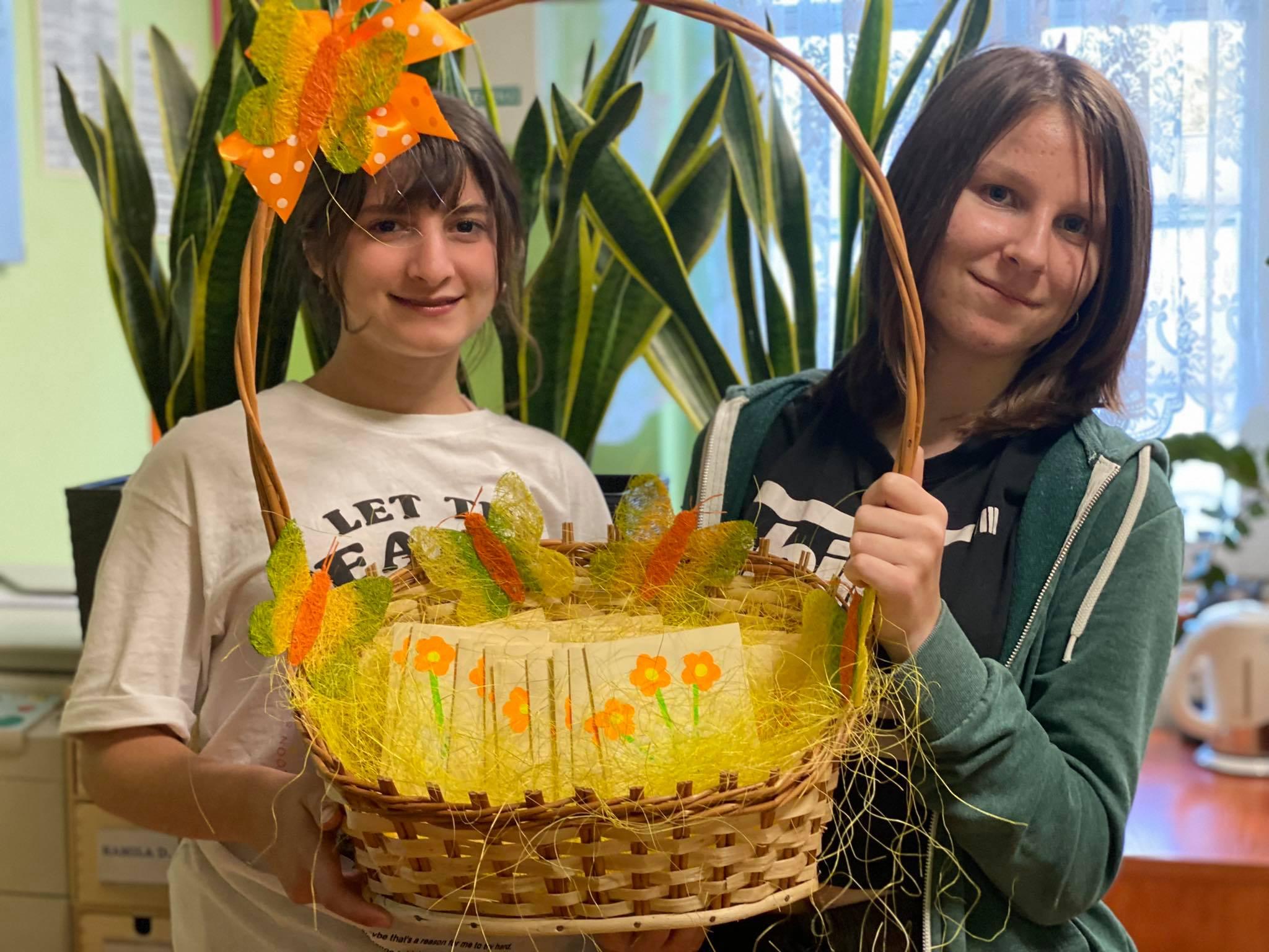 dwie wolontariuszki Źródełka trzymają koszyki z laurkami dla Seniorów