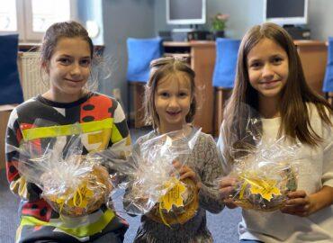 Trójka dzieci trzyma upominki o okazji Dnia Nauczyciela