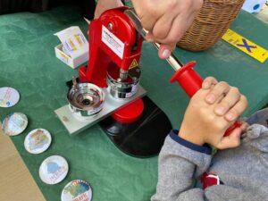 Maszynka do robienia przypinek i gotowe przypinki z logiem jarmarku