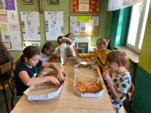 Grupa dzieci w Źródełku je pizzę
